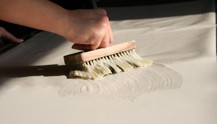 Nakładanie kleju na tapetę za pomocą szerokiego pędzla