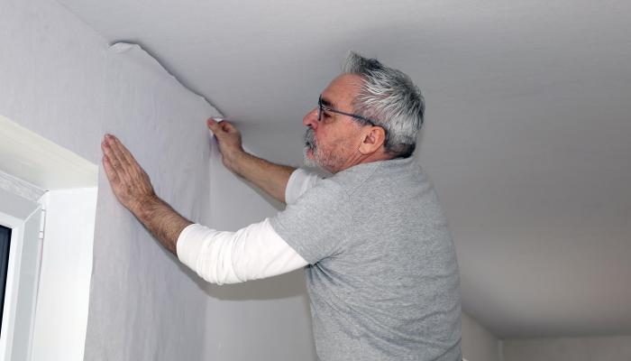 Przyklejanie tapety na ścianie