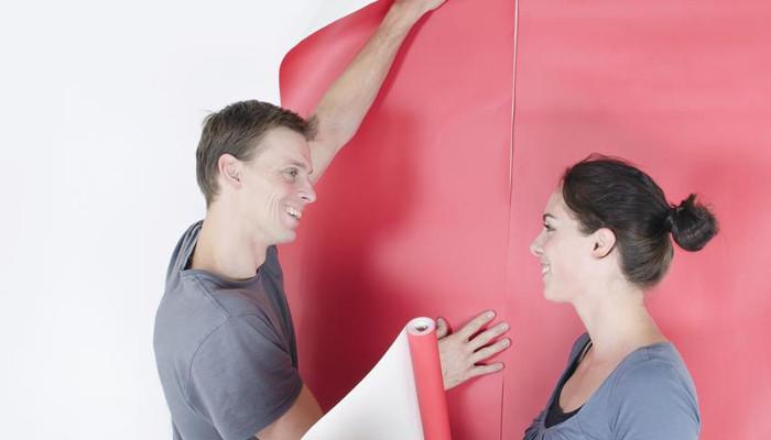 Para zdejmująca ze ściany starą, czerwoną tapetę